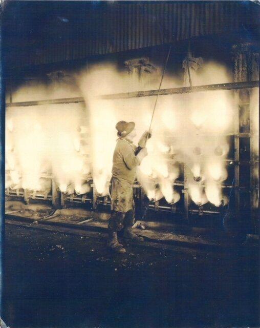 A zinc worker opens an air vent above the retorts.