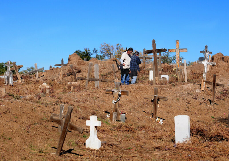 Two Taos Pueblo men tend to their community cemetery in New Mexico.
