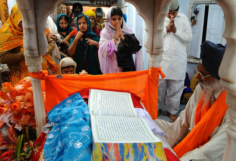 Pakistani and Indian Sikh devotees gather around a priest reading from the Sikh holy book to celebrate the birthday of Sri Guru Nanak Dev, in Nankana Sahib.