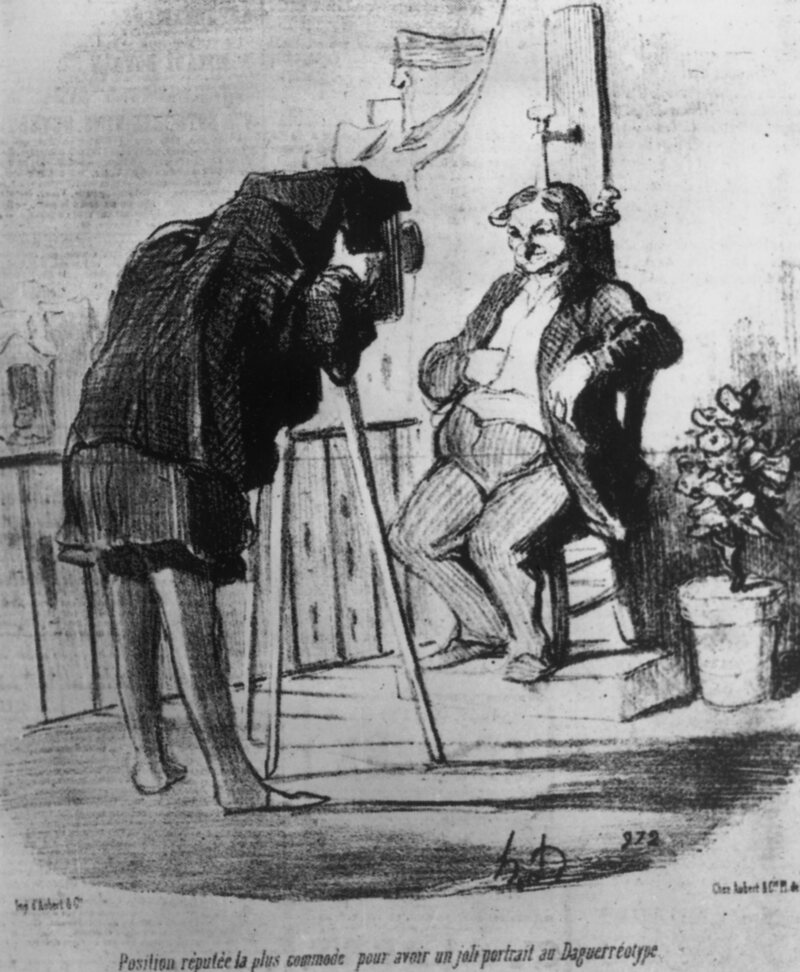 "A cartoon of a man clamped to chair; the caption reads, ""The Position supposed to be the most comfortable for getting a nice portrait in Daguerreotype."""
