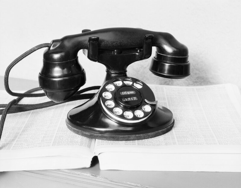 An old rotary dial telephone resting on a directory, c. 1930s.