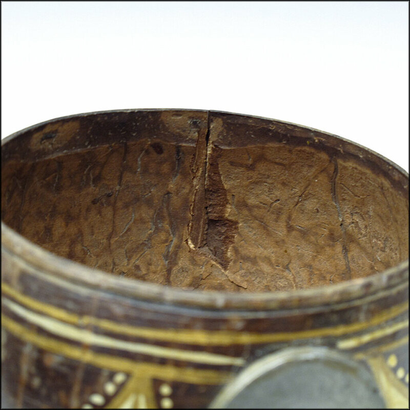 A close-up of an antique coconut dipper.