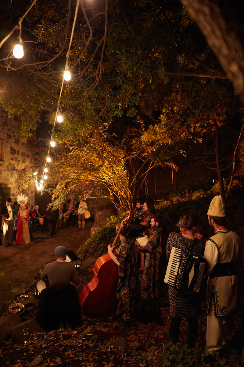 Musicians congregate on the castle's lush grounds.