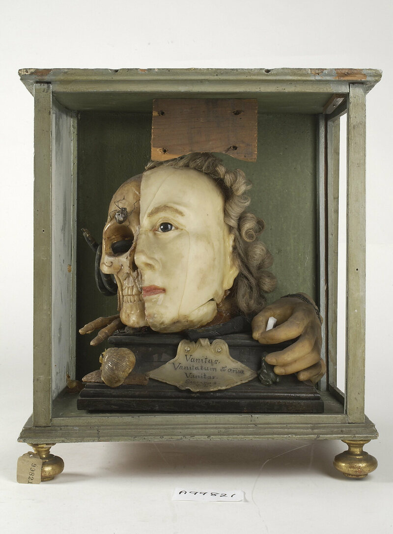 "An 18th-century wax tableau, with one half resembling Queen Elizabeth I, the other a skull crawling with insects. The text below is drawn from Ecclesiastes 1:2, ""Vanity of vanities, is all vanity."""