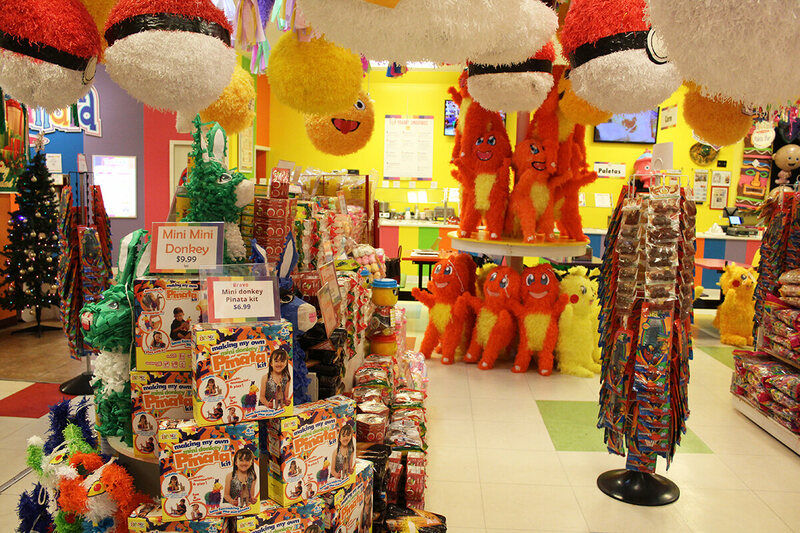 Character piñatas hang from the ceiling and an assortment of piñatas and piñata kits are on the left. Mexican candy on the right.