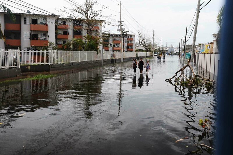 Families picked their way through the flooded streets of San Juan after Hurricane Maria.
