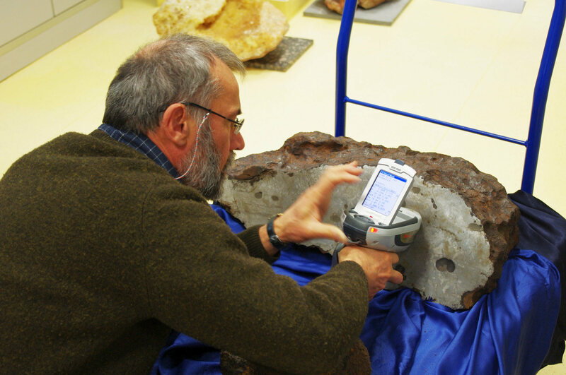 Albert Jambon assesses the metallic composition of a large meteorite from the Morasko Meteorite Nature Reserve in Poland.