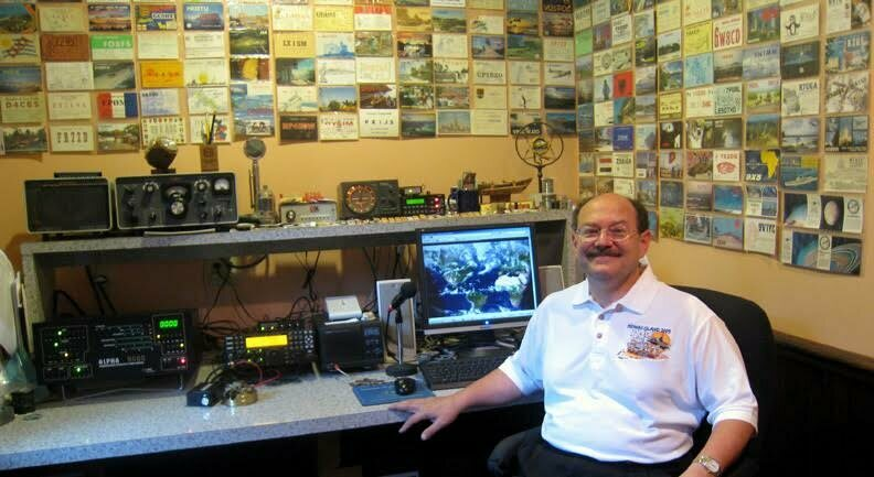 Don Greenbaum with his radios, in front of postcards from all the places he's called.