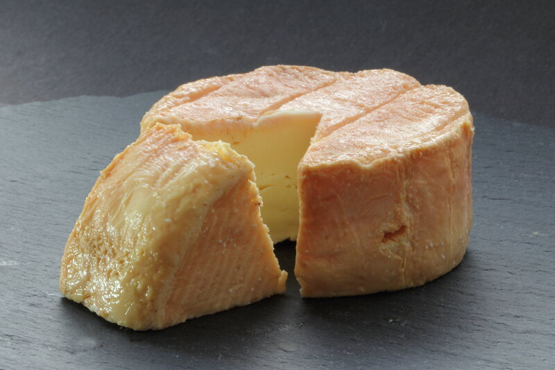 Muenster has a creamy interior and a characteristic red-gold rind.