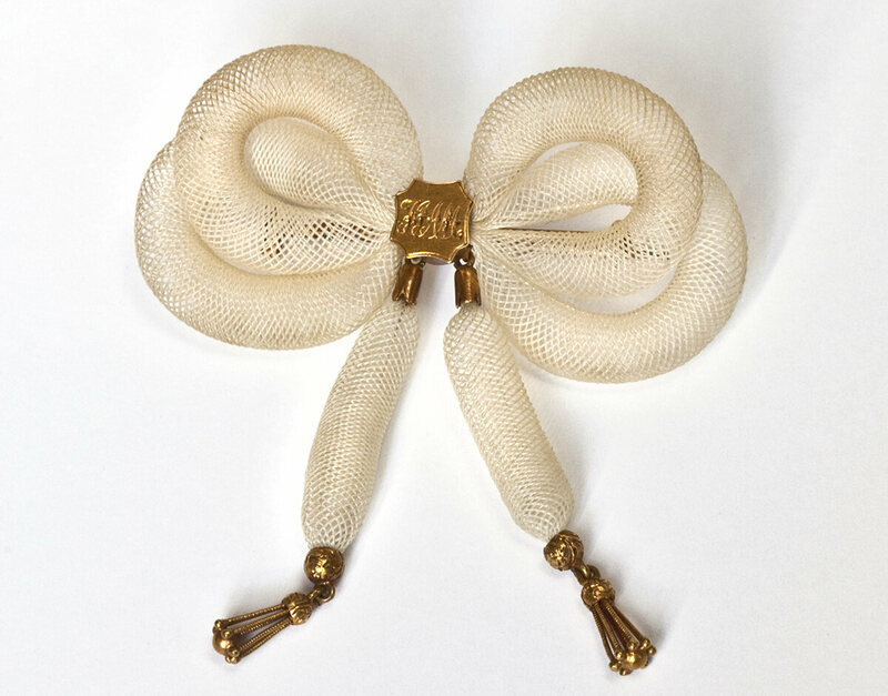 A monogrammed brooch made of gold and human hair using table work, late 19th century.