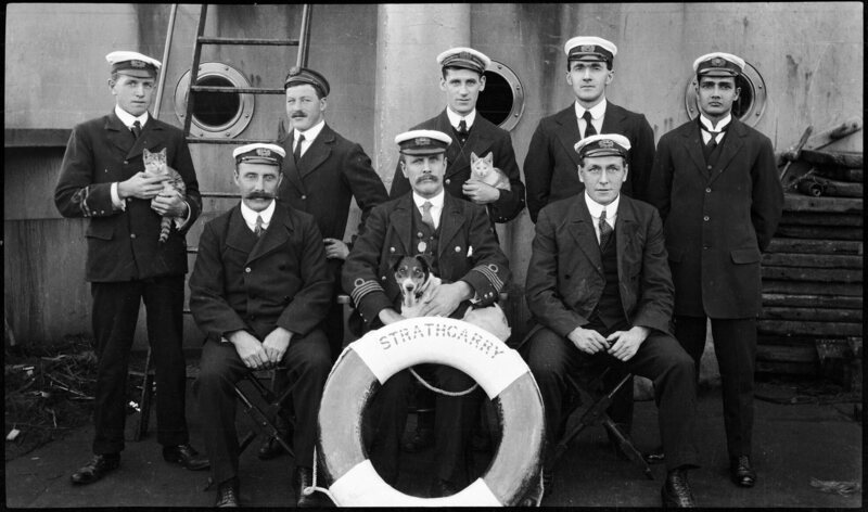 The crew of Scottish steamer SS <em>Strathgarry</em>, with the captain's terrier and two cats.