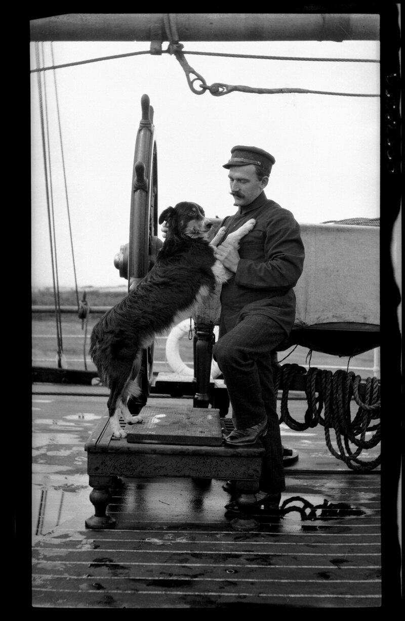 An Australian officer with a pet dog at the ship's wheel, 1907–28.