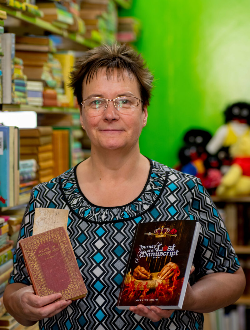 Lorraine Smith in her shop with the deed, <em>Alice in Wonderland</em>, and her own book about her investigation.
