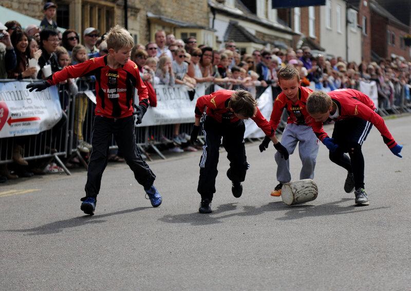 A team of children wheel a block of wood down the street in Stilton, England.