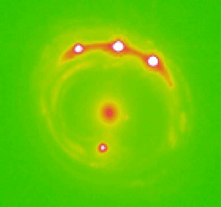The RX J1131-1231 galaxy (at center) with four quasars lensed around it. Scientists identified evidence of 2,000 planets wandering in this elliptical galaxy.