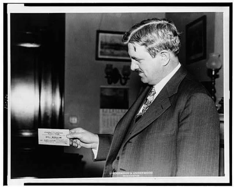 Senator Clarence Dill holds a piece of Tenino's wooden money.