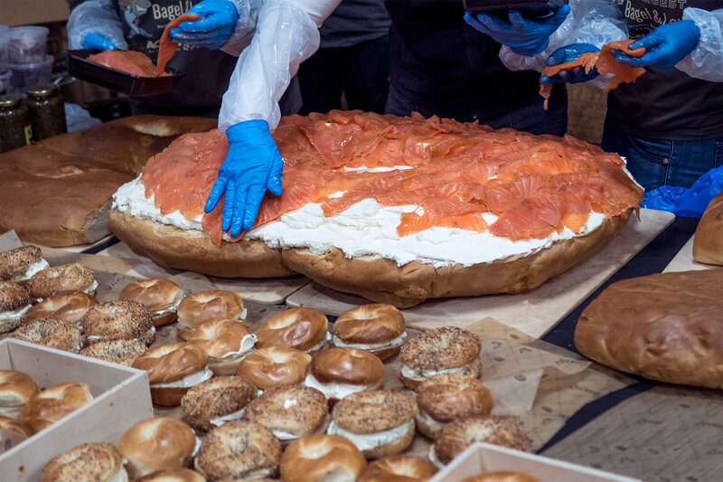 Assembling the gigantic bagel and lox.