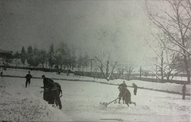 Players clearing snow from the Pyongyang Foreign School land ice rink, with the low boards visible behind them.
