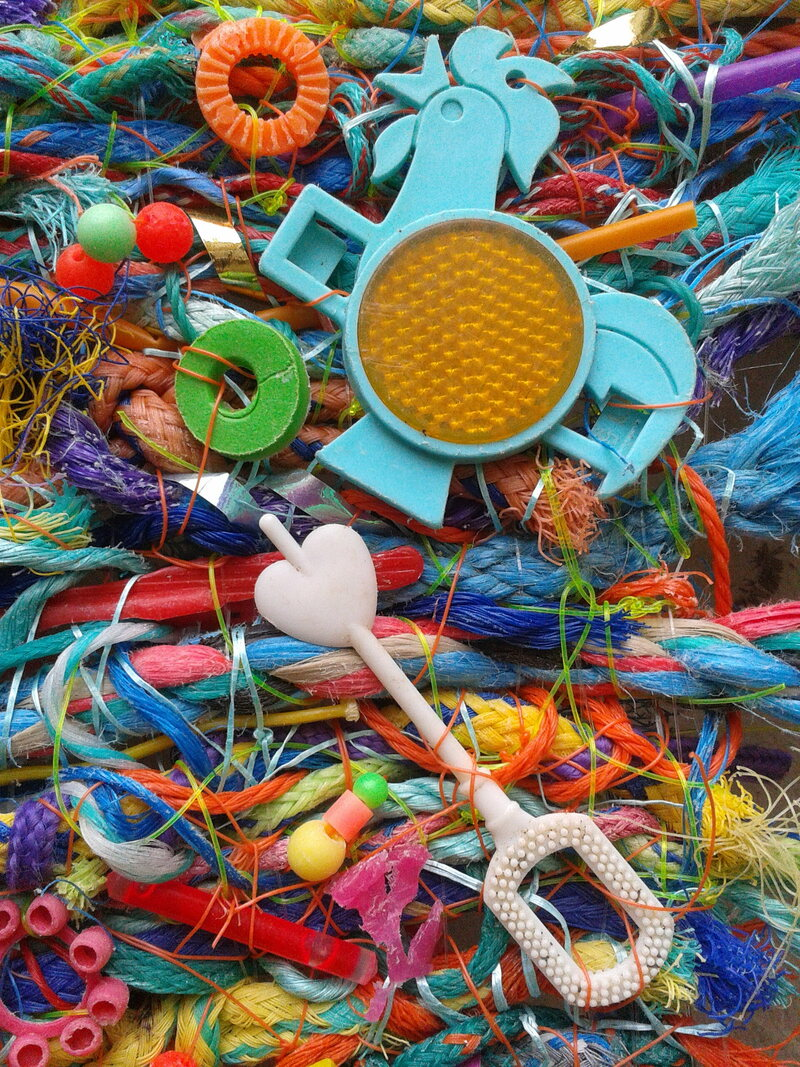 A detail from a flotsam weaving, featuring a bubble wand and a rooster-shaped bike reflector that once came free in boxes of Kellogg's Cereal.