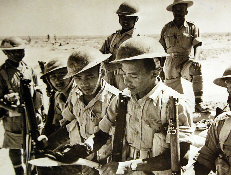 A Gurkha soldier cleaning his Kukhuri in the Western Desert, July 1942.