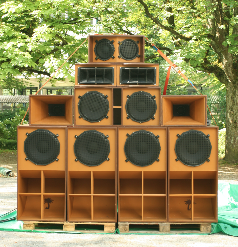 A sound system with four subwoofers on the bottom, one low-frequency box flanked by two mid-frequency horns, two high-frequency sectoral horns, and one mid-high box on top.