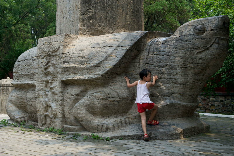 A girl stands by a Bixi at Dai Temple in Shandong, China.