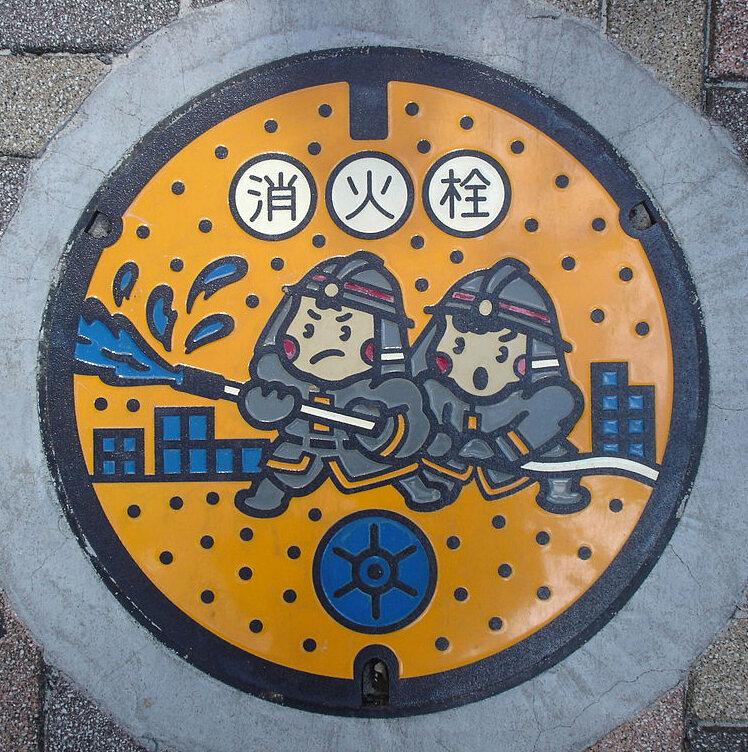 "A manhole cover in Tokyo depicting ""fireboys."""