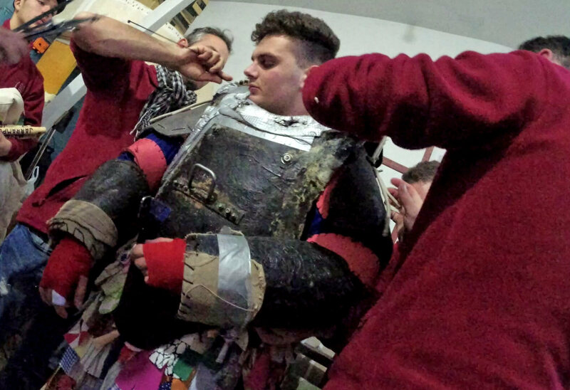 Nineteen-year-old Adrián Moreno Serrano's <em>mayordomos</em>—family and friends—help gird him for battle in a costume that weighs more than 100 pounds.