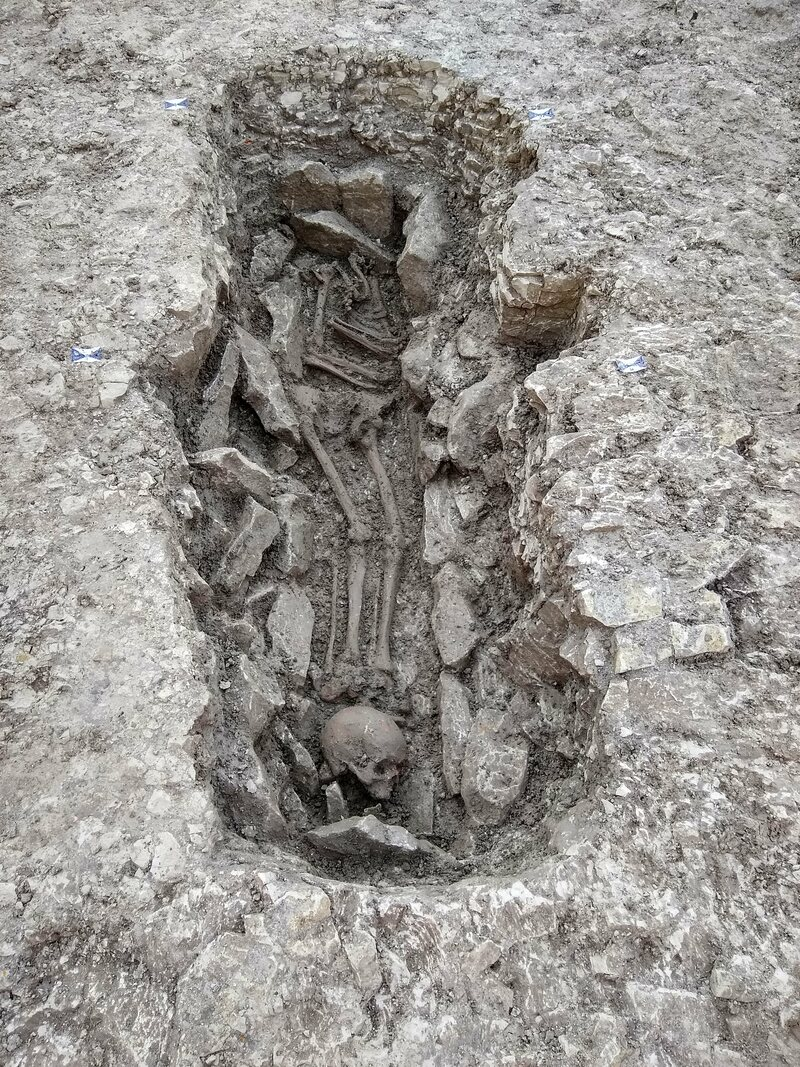 A skeleton with its skull placed at its feet.