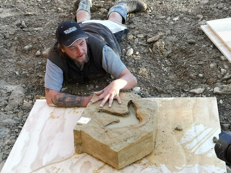 Michael Johnston poses with one of the newly discovered footprints, freshly extracted from the ground.
