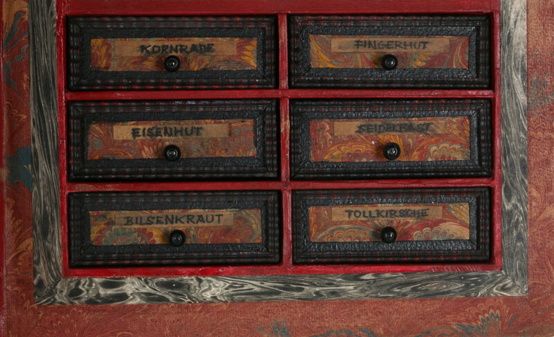 The little drawers include the German words for foxglove, belladonna, and other potential poisons.