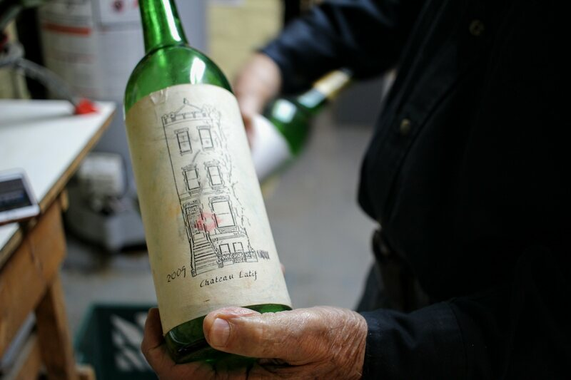 Jiji holds a sample bottle, whose contents were long ago imbibed.