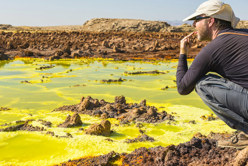 A tourist tastes salt water with his finger at Dallol's hot springs.