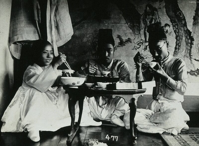 A group of people enjoying a meal in 1900.