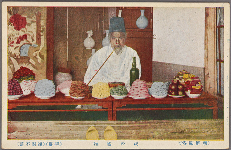 A shopkeeper in Seoul selling piles of festival treats, in the early 20th century.