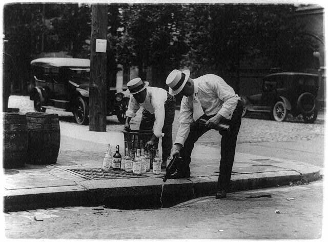 Men pour whiskey into a sewer during American Prohibition.