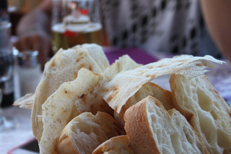 Crispy pieces of carta di musica rest atop a bread basket.