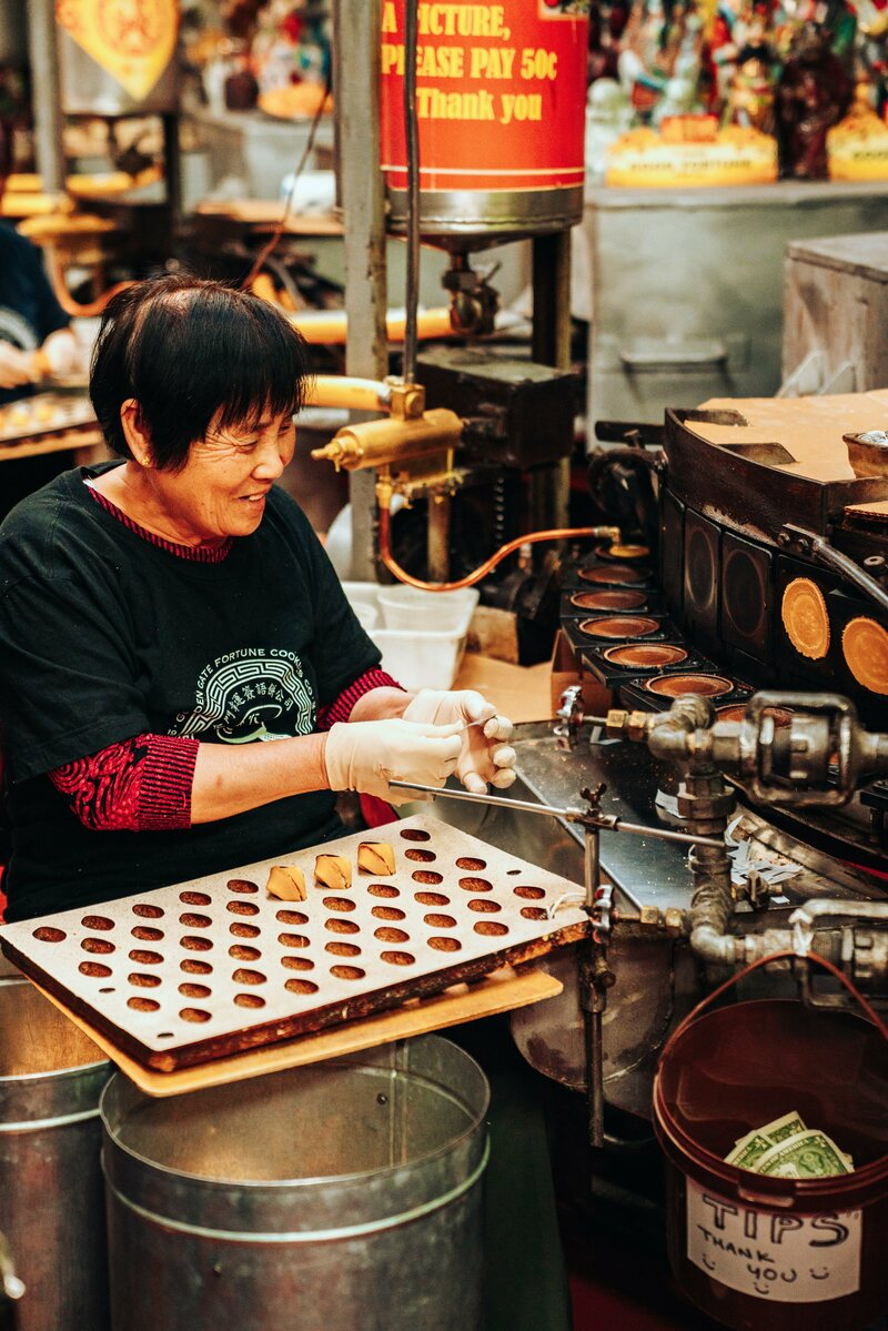 A woman makes fortune cookies—adopted by Chinese restaurants in response to Americans' expectations of dessert—at Golden Gate Fortune Cookie Factory in San Francisco.