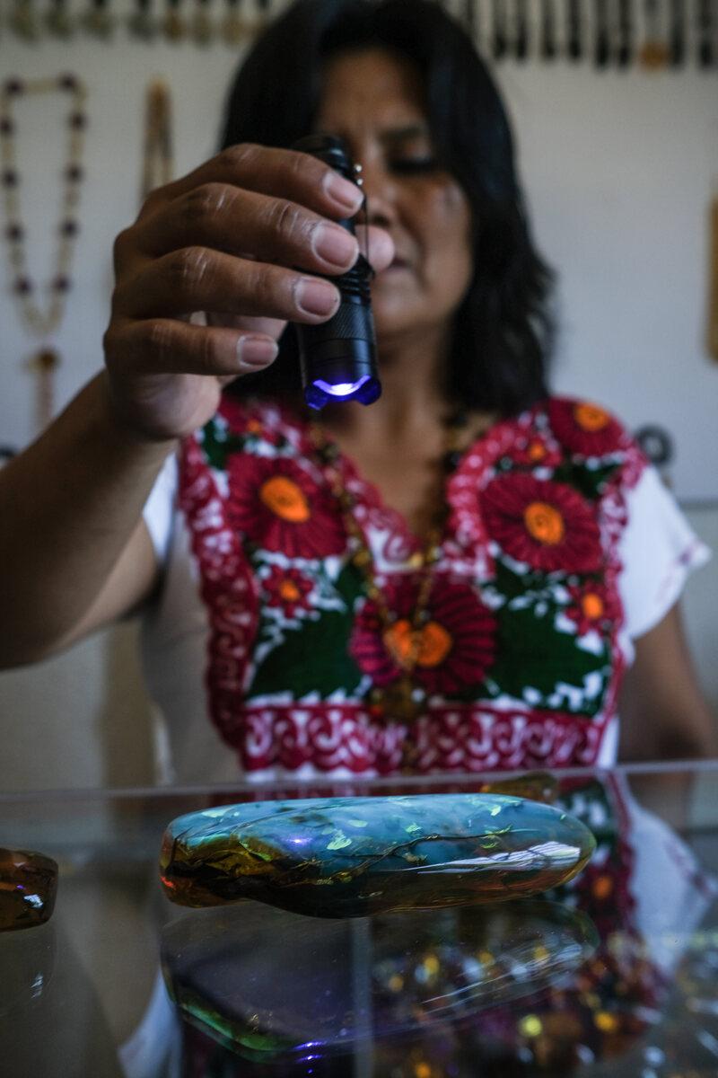 Amber naturally fluoresces under black light, as demonstrated by Patricia Diaz Ruiz, an amber dealer in Simojovel.