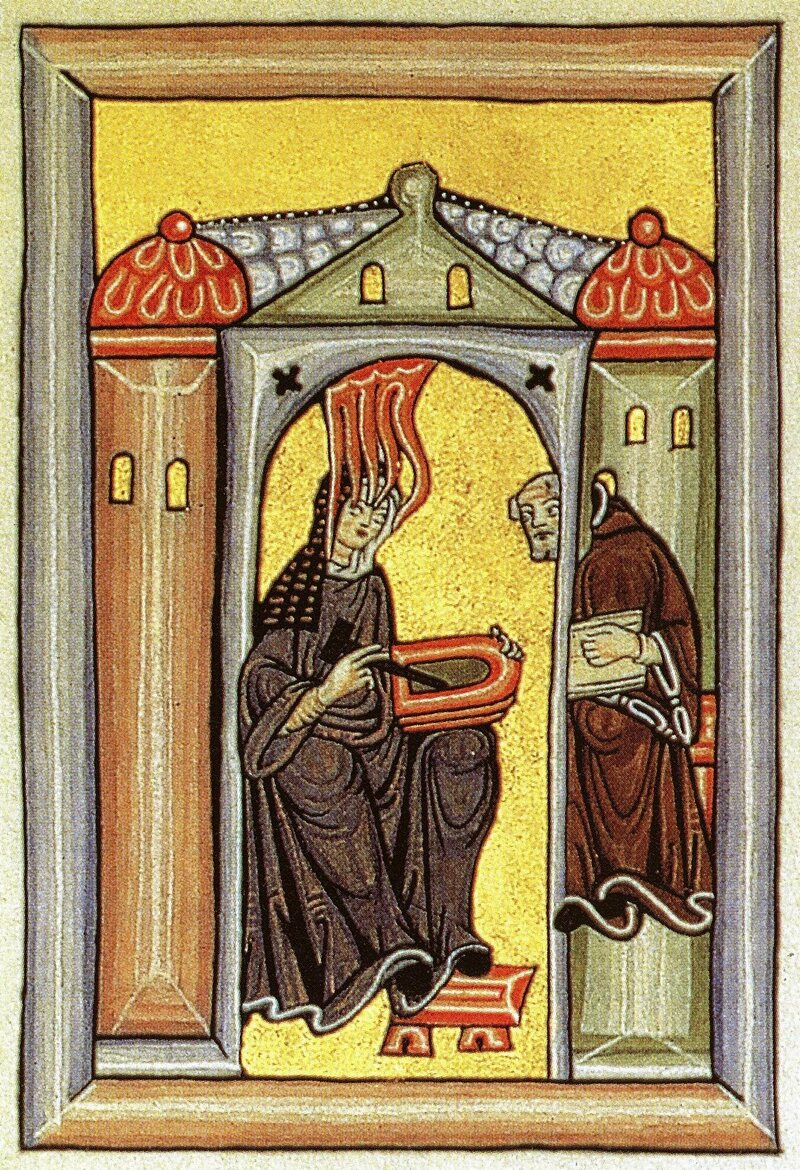 An illustration from one of Hildegard's visionary texts, depicting her receiving a vision and dictating to her scribe.