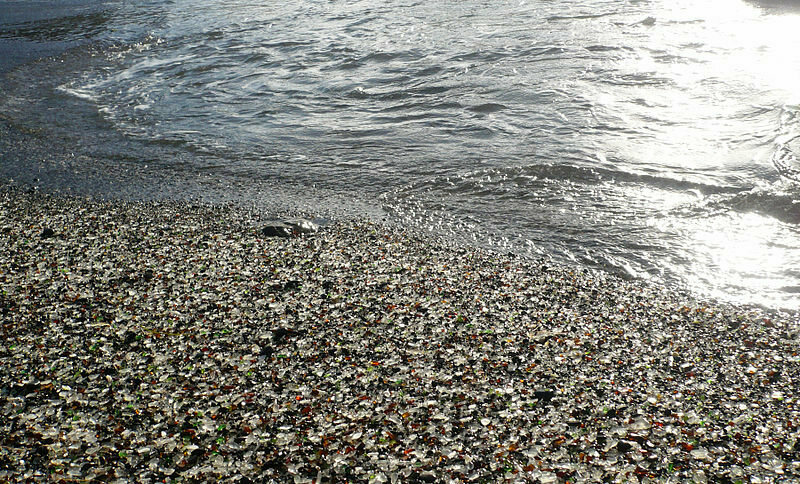 The waves wash over the mix of rocks and ground-down glass pieces on the site of a former trash dump, now Glass Beach in Fort Bragg, California