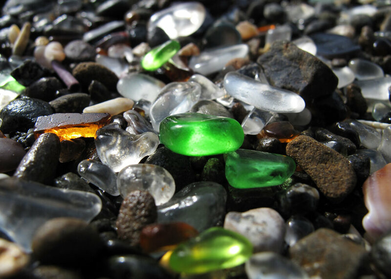 A close-up of glass pebbles worn down by ocean waves, originally pieces of bottles and dishes, on Glass Beach in Fort Bragg, California.