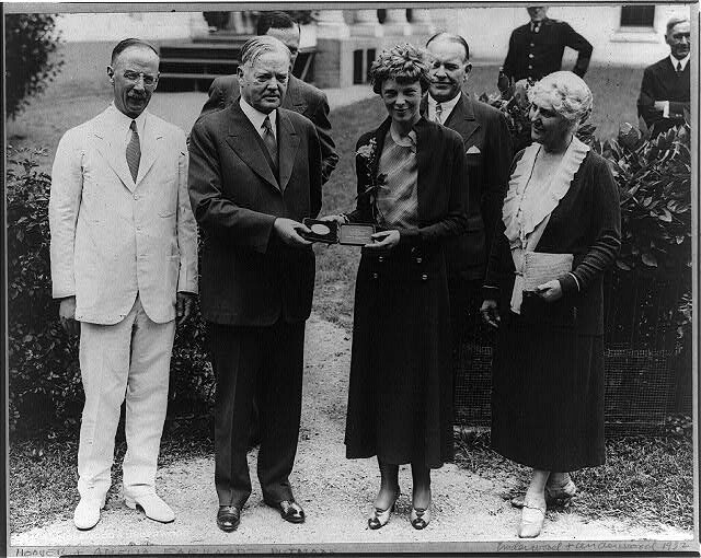 President Hoover presenting the National Geographic Society gold medal to Earhart recognition of her non-stop solo flight across the Atlantic Ocean