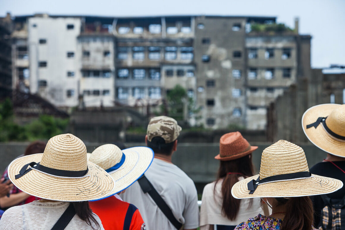 Japanese tourists get a quick look at a decaying building.