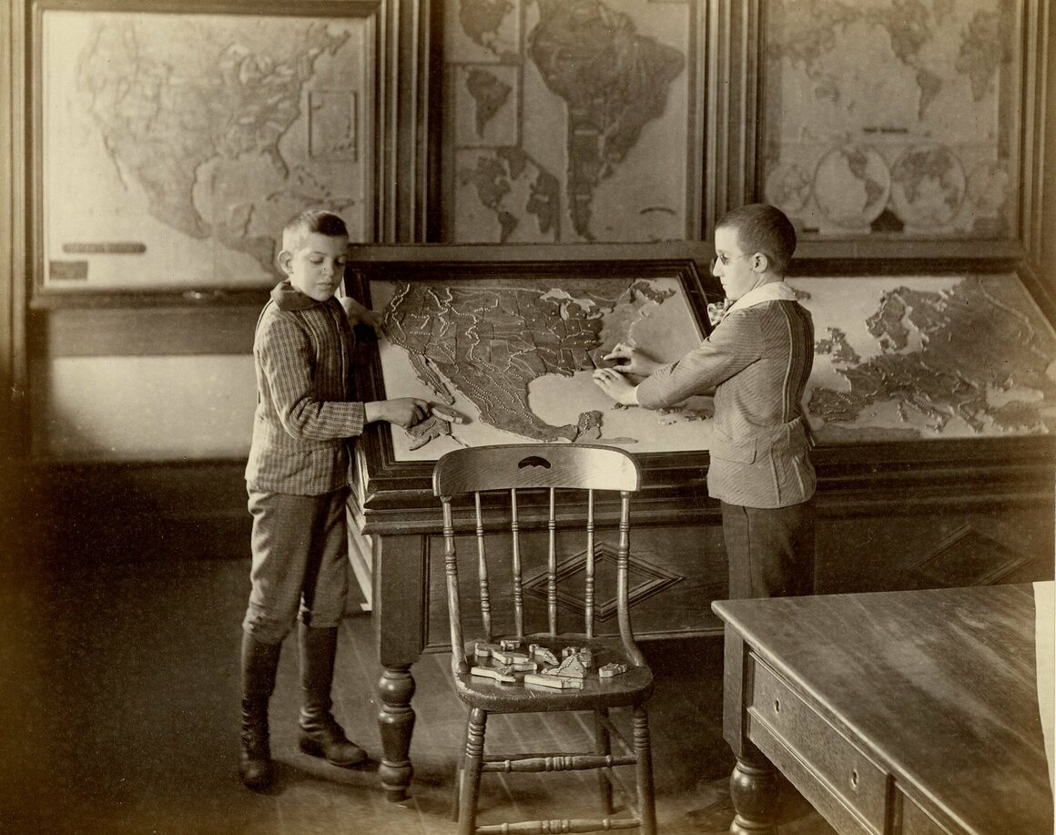 Two schoolboys piece together a map of the United States.