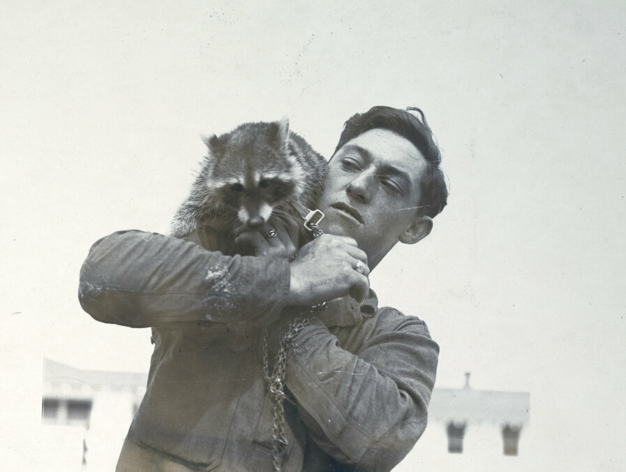 A raccoon on the shoulder of a soldier stationed at Carlstrom Aviation Field in Arcadia, Florida.