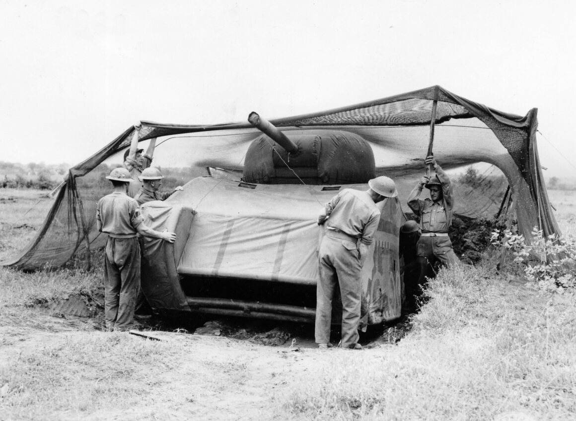 British soldiers place a dummy tank into a camouflaged position.