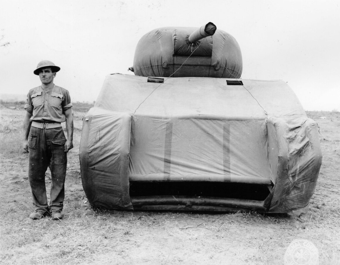 A soldier stands next to a British dummy tank.