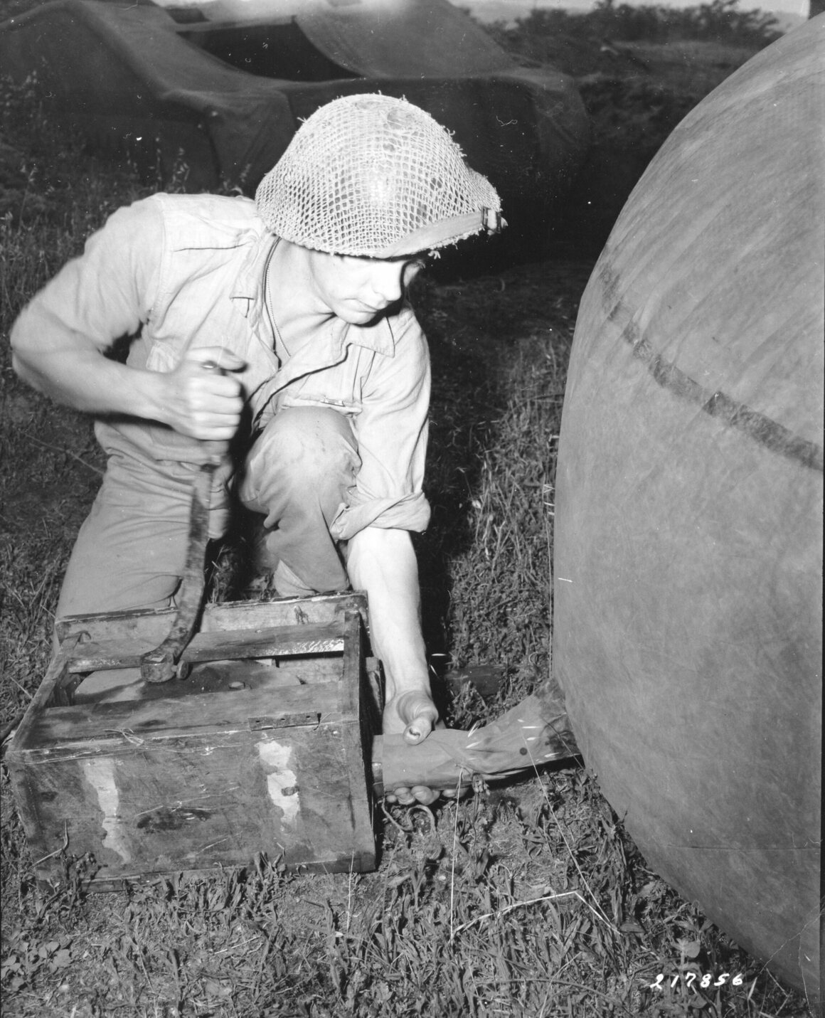 A British army engineer uses a forge pump to inflate the turret of a rubber dummy tank. The tanks were designed and used by the British to simulate tank positions in the field. Taken in Italy in 1944.
