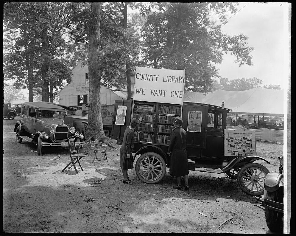 "Mobile library, with the sign ""County Library: We Want One,"" Rockville Fair, Maryland, 1928."